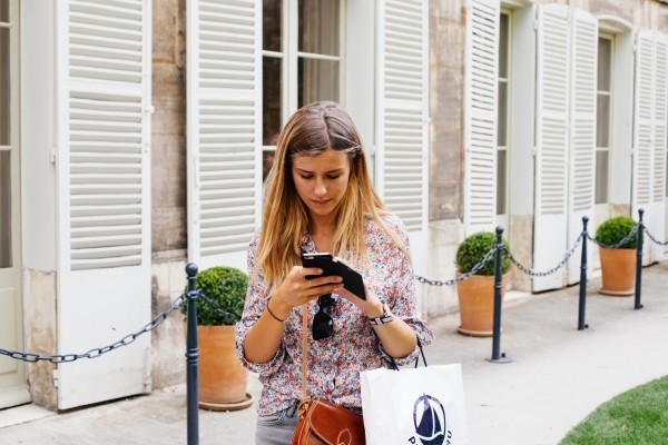 young-woman-text-messaging-on-street