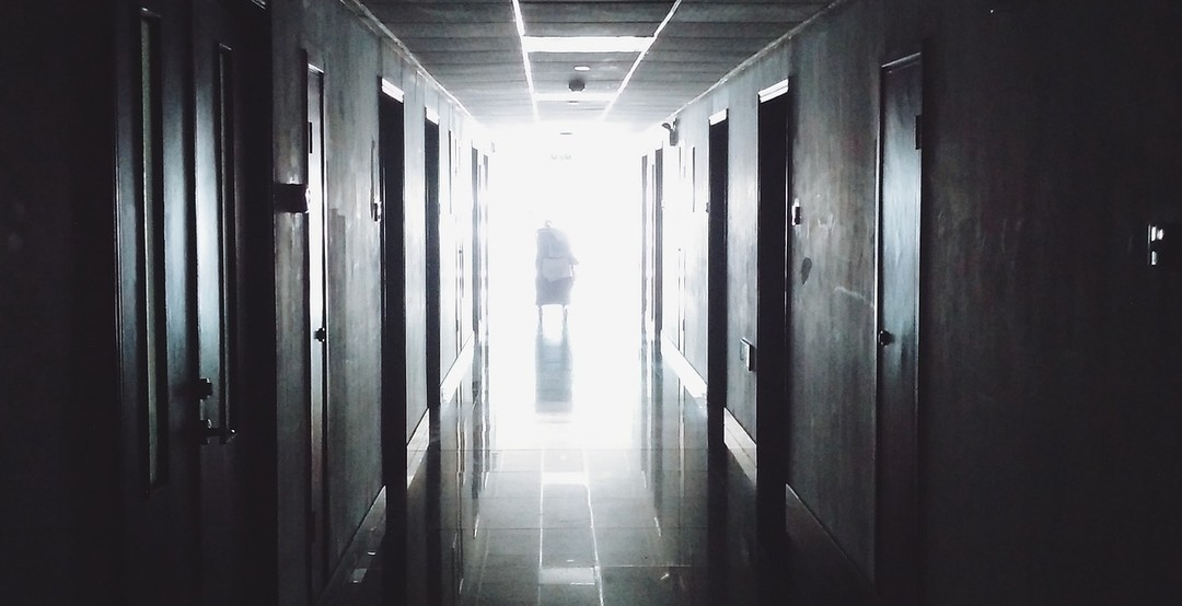 灰暗的醫院走道,走廊的深處傳來光